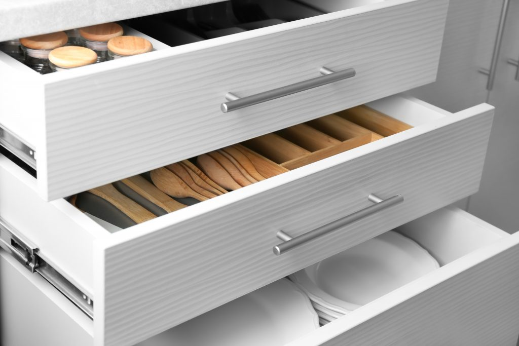 White, open kitchen drawers showing set of ceramic plates and utensils