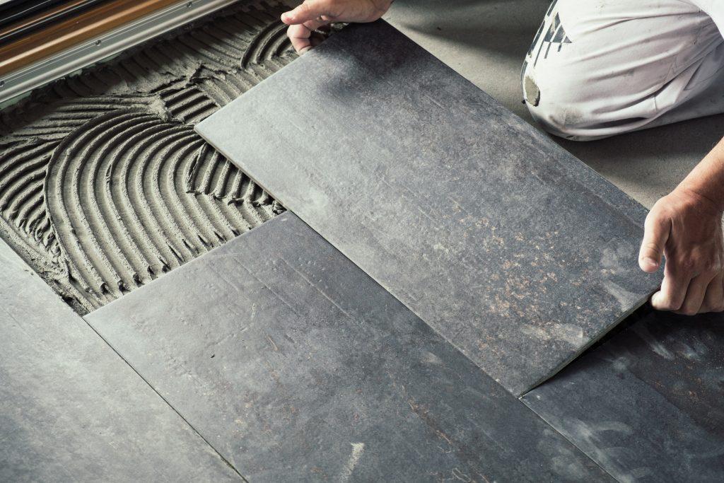 worker laying down ceramic floor tiles