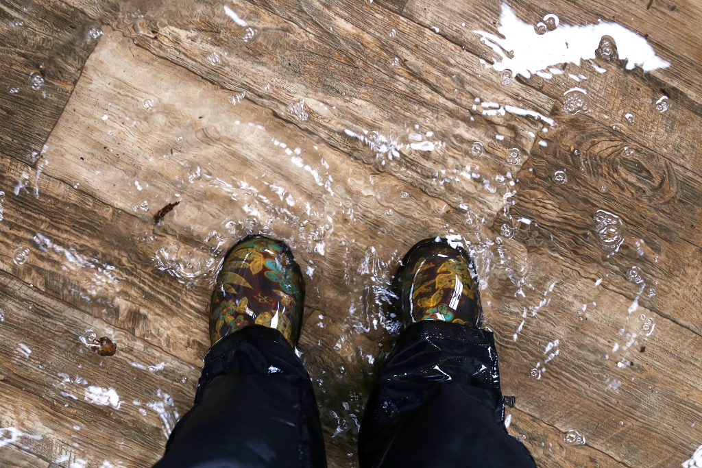 Woman's feet, wearing waterproof rain boots standing in a flooded house with vinyl wood floors, how to spot water damage on wood floor