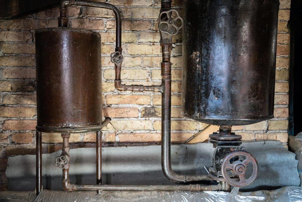 4 Signs that Your Water Heater Needs Replacement, Rusty boiler room pipes. Old metal boiler generating heating and delivering it to home through pipeline. Hot water or gas is being delivered with this system