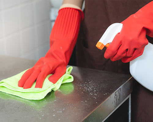house maid cleaning sink in the kitchen with sponge and cleanser, stainless steel cleaning