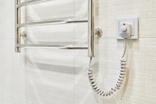 Modern heated towel rail on tiled socket bathroom wall